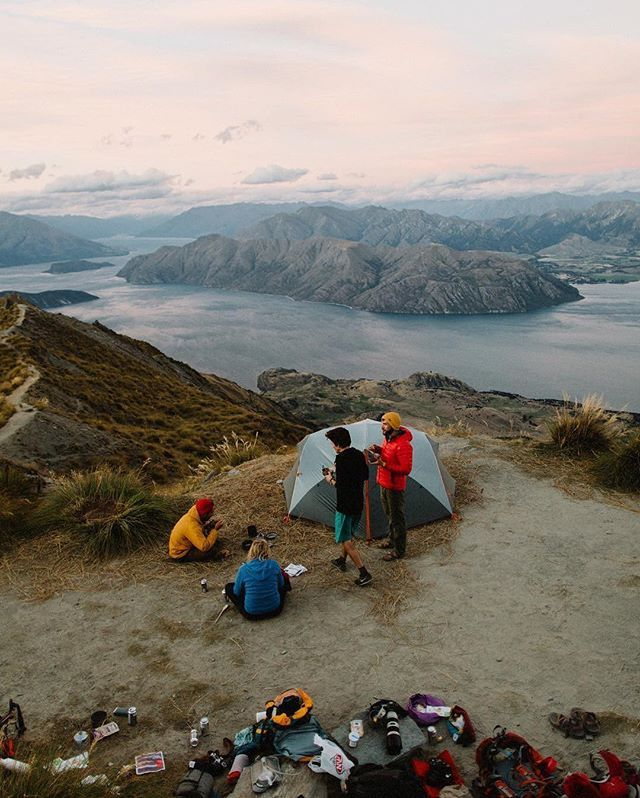 """Dinner is best served with good friends, a cozy tent, and scattered gear. Epic views and sunsets are optional, but highly recommended."" Photo by @gregbalkin on Roy's Peak, overlooking Lake Wanaka in #NewZealand. #OptOutside"