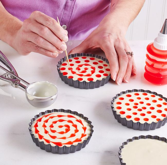Pipe small strawberry glaze dots onto the still wet cheesecake in a swirl pattern. Then run a toothpick through the center of each dot to create a string of hearts.