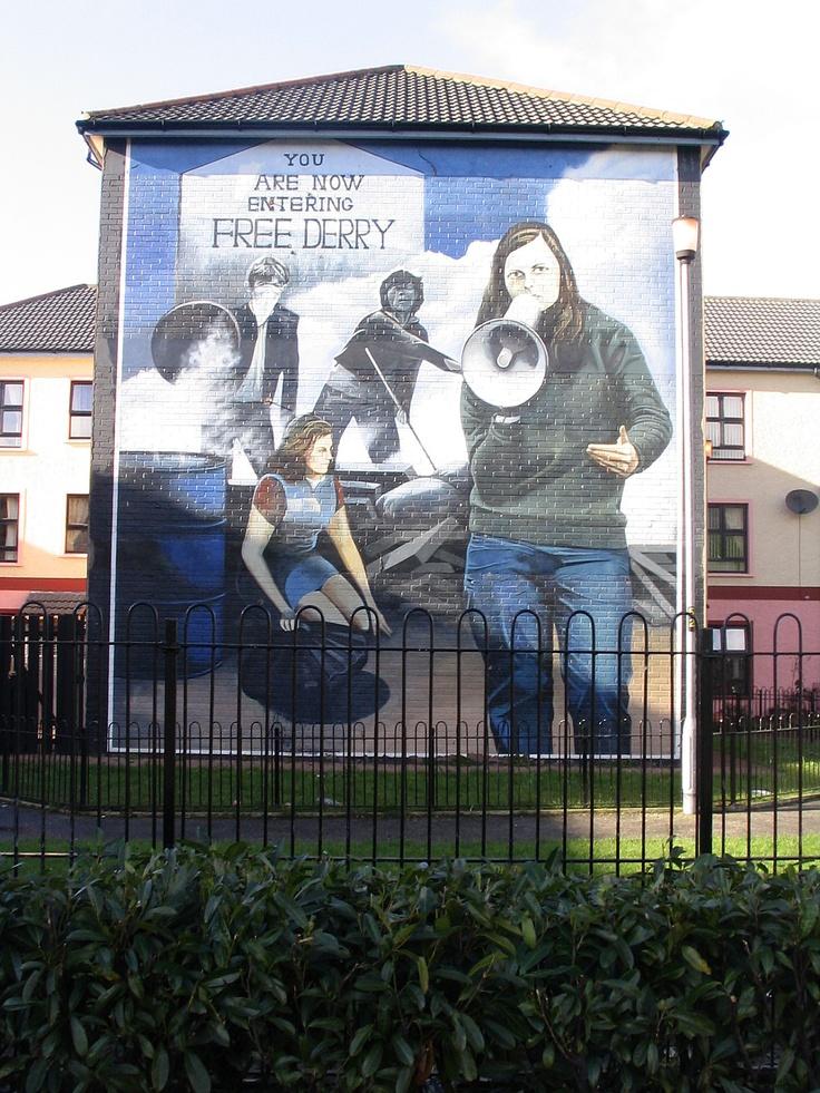 Le personnage à droite avec le mégaphone, c'est Bernadette Devlin qui était avec son groupe d'étudiants People's Democracy, une des leaders dans la lutte pour les droits civiques.  Au-dessus d'elle, il y a deux émeutiers. Et enfin, le fameux mur portant l'inscription : Vous entrez maintenant dans le Derry libre qui existe toujours et est régulièrement repeint. Il se trouve à dix mètres de ce mural.