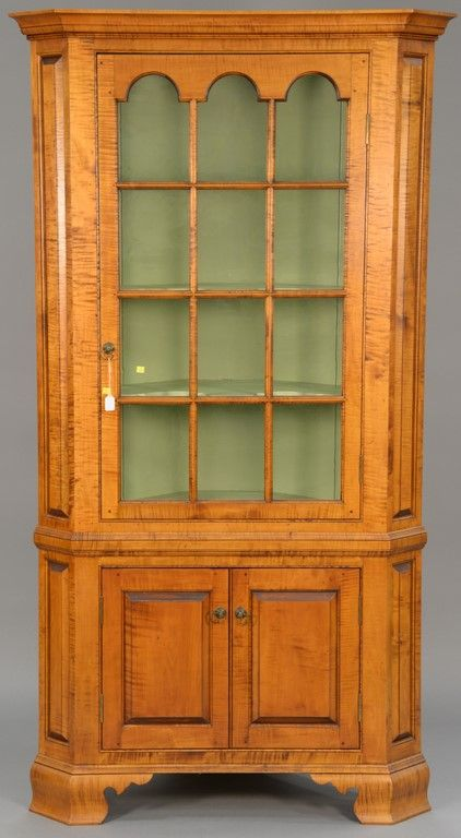 D. R. Dimes custom tiger maple corner cabinet in two parts, upper section with twelve glazed glass panels on base with two doors set on ogee feet, 20th century, signed on reverse.  Realized Price $4,020.00