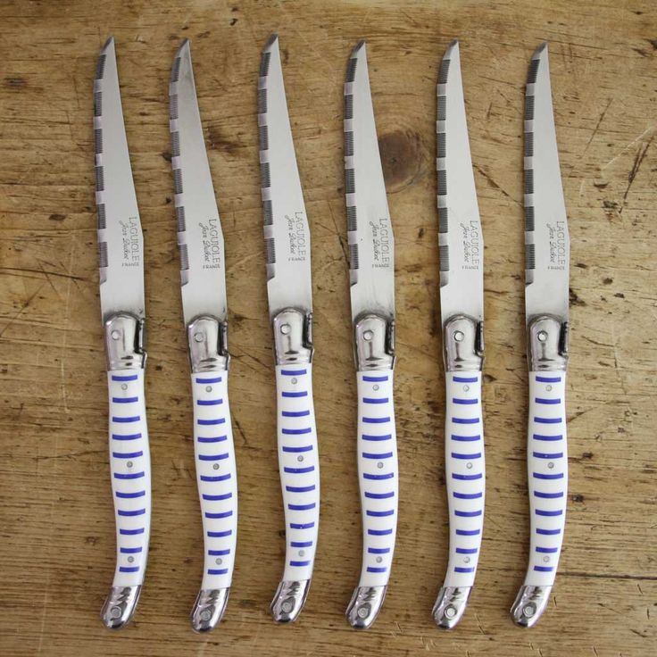 A fun boxed set of six traditional Laguiole steak knives with blue and white striped handles. Made in Thiers, an ancient town in central France famous for its cutlery industry. Because Laguiole descri