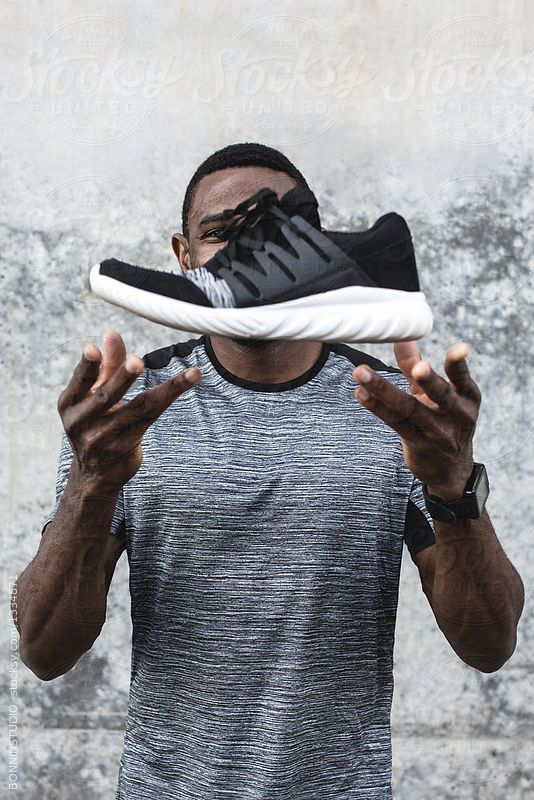 Male athlete throwing up his black sneaker. by BONNINSTUDIO for Stocksy United