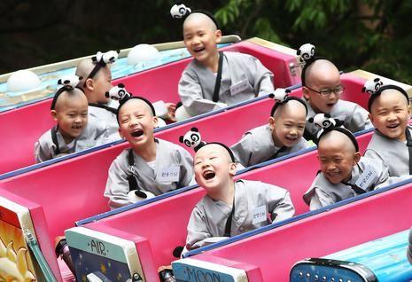 Jeugdige monniken genieten van een ritje in de achtbaan. De jonge monniken volgen een spoedcursus in boeddhisme in Seoel, Zuid-Korea.