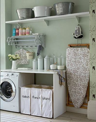 laundry room. Love the glass jars for soap and the retractable drying rack above the washer