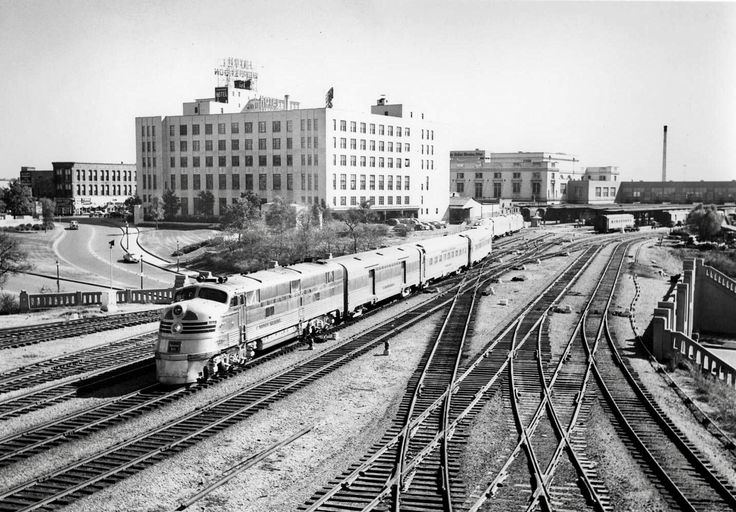 The Sam Houston Zephyr passenger train shown crossing over the Triple Underpass, heading out of Dallas, Texas, 1950. The Post Office Terminal Annex is the tall white building, the Jefferson Hotel is behind it (with the sign on its roof), and Union Station is in the background, just right of center, with the Dallas Morning News building peeking over its roofline. The Old Red Courthouse would be out of frame to the left.