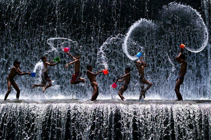 Local boys having a splashing time at the waterfall at Klungklung, Bali