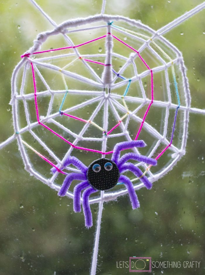 Really simple spider web window decoration. Perfect Halloween craft using yarn, pipe cleaners and a bottle top for the spider.
