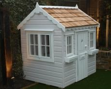 Painted cottage style playhouse with cedar shingle roof