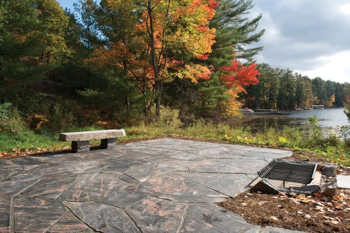 """This Muskoka granit patio project turned an unused waterfront space into one of this families favourite cottace spaces. Featuring 3"""" granite flagstone from our Blue Lake Quarry, this patio area features a fire pit and custom granite slab bench. All product is from the Muskoka Rock Company."""