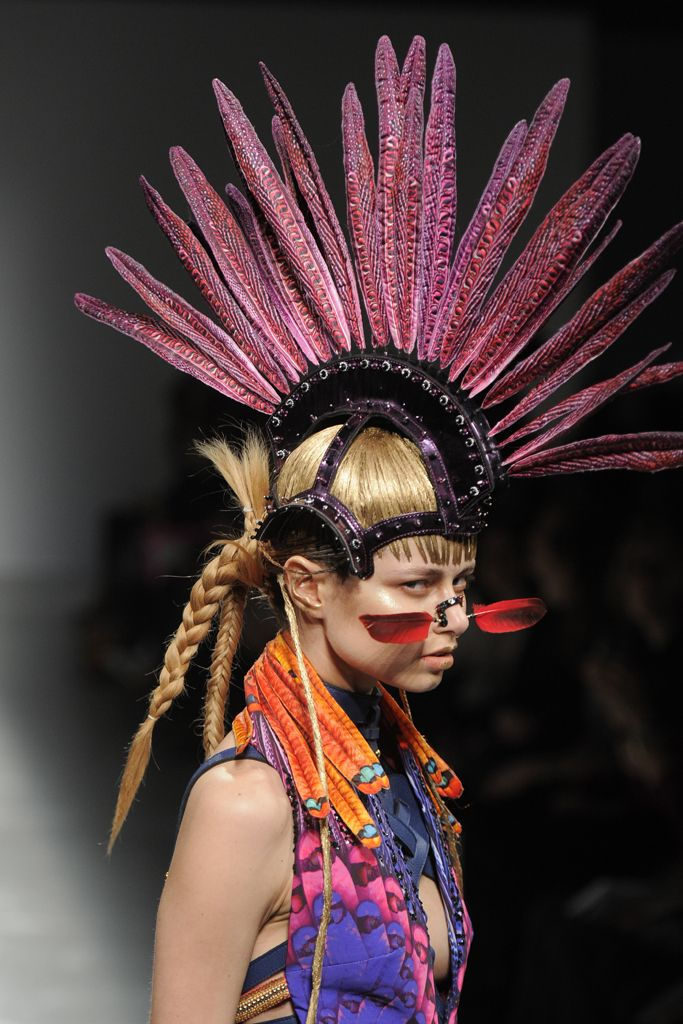 The Manish Arora runway has never been about shrinking violets. This season he took his band of exotic gladiators and gave them a punky edge with skull purses, knee-high combat boots and this over-the-top feather mohawk worn with tribal nose art. [Photo by Dominique Maitre]