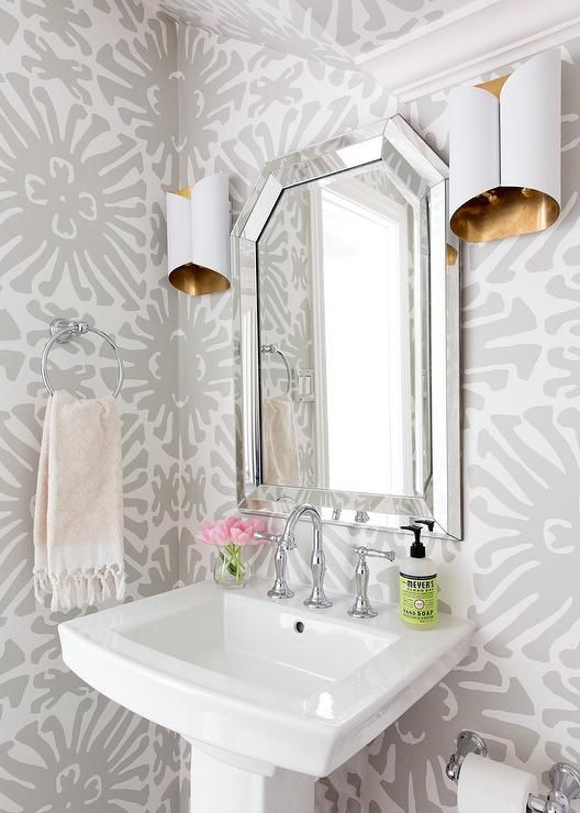Gray and white powder room is clad in white and gray wallpaper and boasts a white pedestal sink fitted with a polished nickel gooseneck faucet kit positioned beneath a beveled mirror flanked by white and gold sconces.