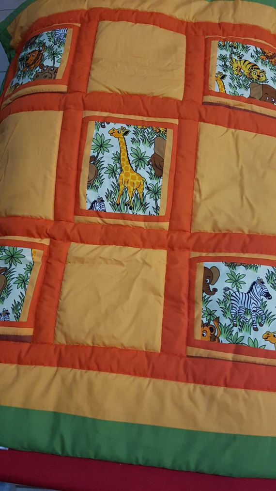 Have a love of wild animals Zebra Lions, Elephants Giraffe fussy cut , 5 patch patchwork quilt. In Earthy tones of orange, greens.  Quilt measures 74 cm wide by 90 cm long Cotton borders and cotton backing. Polyester batting , ideal for little ones with allergies. Completely washable in machine in cold water and hang dry. No bleach or bleach like products At Mean Mothers Creations we can create a one of a kind quilt just for you , please contact us today.