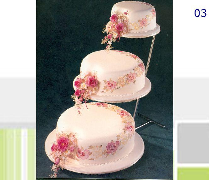 Torta de bodas escalonada forrada en fondant rosa pálido con flores pintadas con pintura comestible y ramilletes de flores naturales. Rellenos a elección