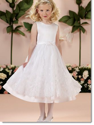Joan Calabrese -  Available to order from Little Angels Couture, this sleeveless satin and tulle tea-length A-line dress with jewel neckline, satin set-in waistband with centre front bow, covered buttons down back bodice, tulle overlay skirt with wide lace appliqué and satin hemline, perfect as a flower girl dress or First Holy Communion dress.