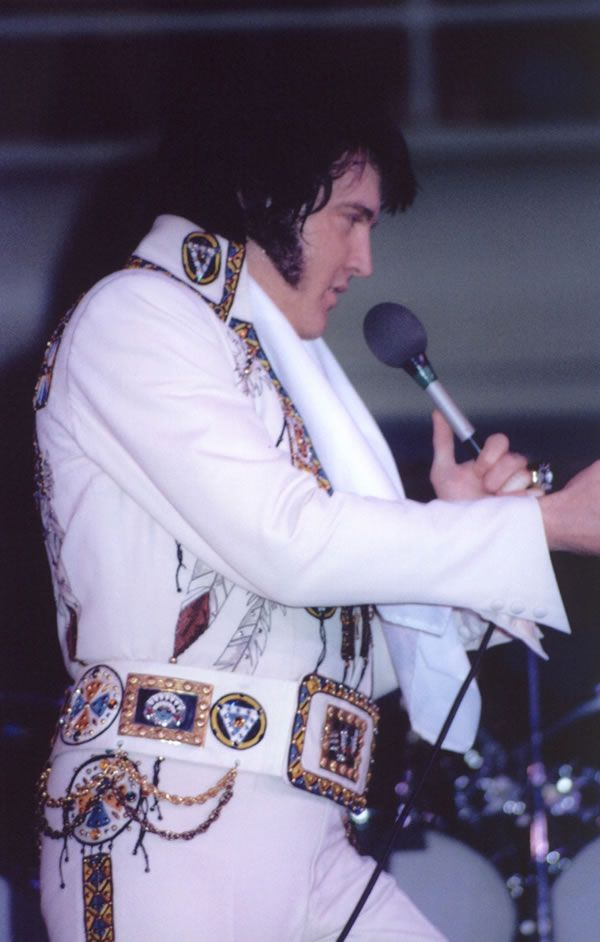 In concert at Coliseum Charlotte NC Feb 21, 1977 wearing chief suit
