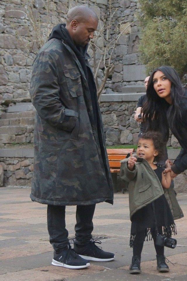 Kanye West wearing Adidas Yeezy Season 1 Camo Trenchcoat , Saint Laurent Skinny Stretch Denim Jeans, Adidas SL Loop Runner Shoes