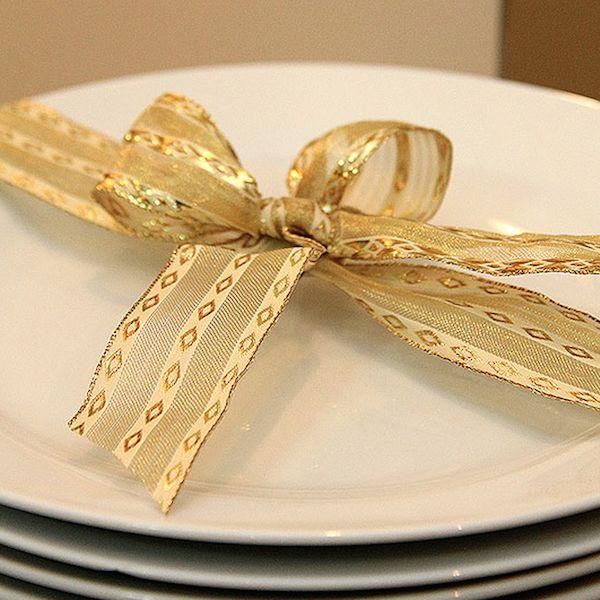 """Uma ideia inusitada para as ceias de fim de ano é """"embalar"""" os pratos dos convidados – isso é um sinal de que a ceia vai ser um verdadeiro presente! Fitas douradas ou prateadas dão um toque sofisticado. Depois, é só caprichar no cardápio!"""
