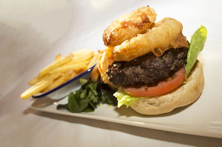 Home-made 8oz Steak Burger served on a toasted brioche bun with lettuce, tomato and skinny fries with a side order of onion rings