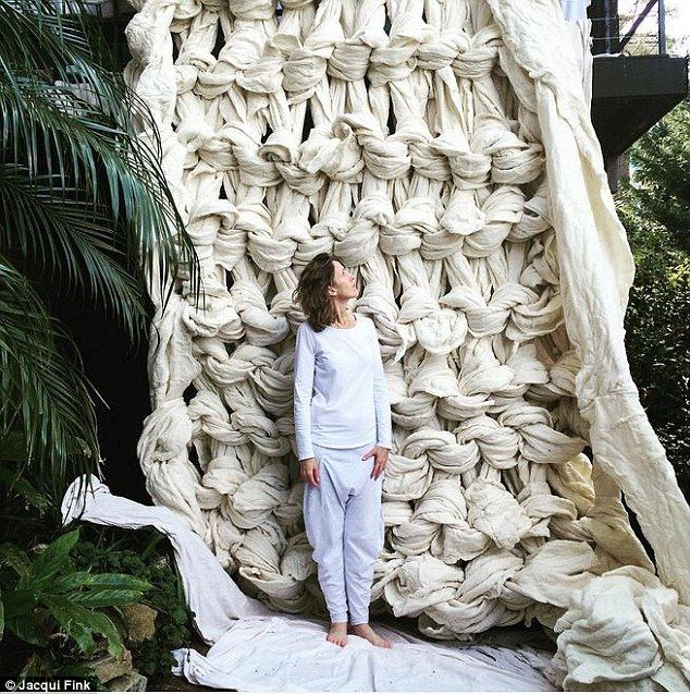 Aussie mother, Jaqui Fink, stands in front of a giant arm knitted wall hanging made from Australian merino wool