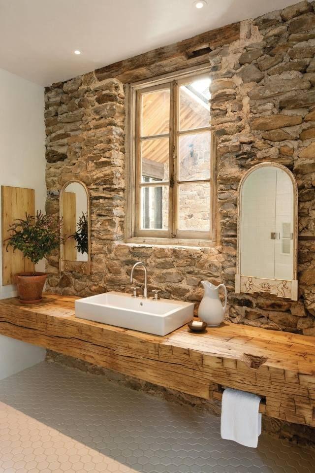 Plan vasque en bois naturel  avec un revêtement mural en pierre.