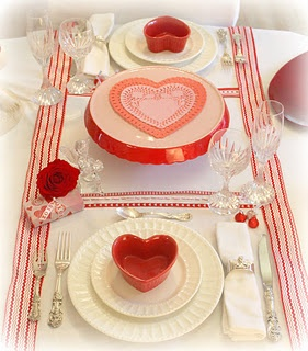 St. Valentine's Day table setting red heart ramekins on white ironstone.  Crystal goblets, silver flat ware. Red & white ribbon on table.
