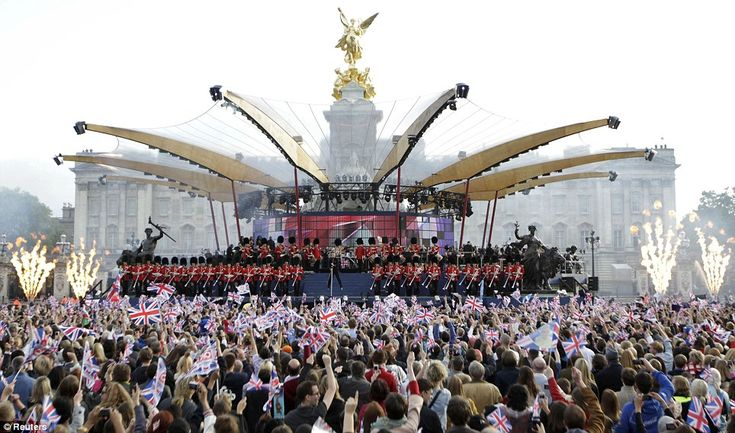 Spectacular: Spectators wave Union Flags as they watch singer Robbie Williams perform during the Diamond Jubilee concert in front of Buckingham Palace