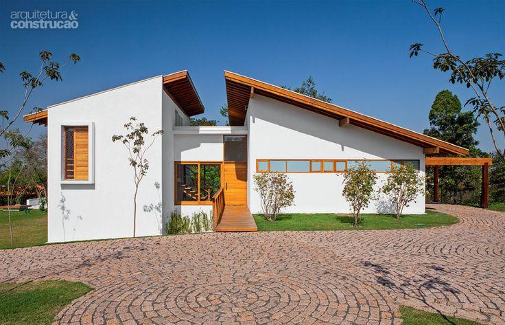 Casa incorpora árvore no deck e se beneficia de sua sombra_No centro, marcado pela porta com passarela de freijó, fica a entrada, cuja laje dá acesso às caixasd'água e aos aquecedores.
