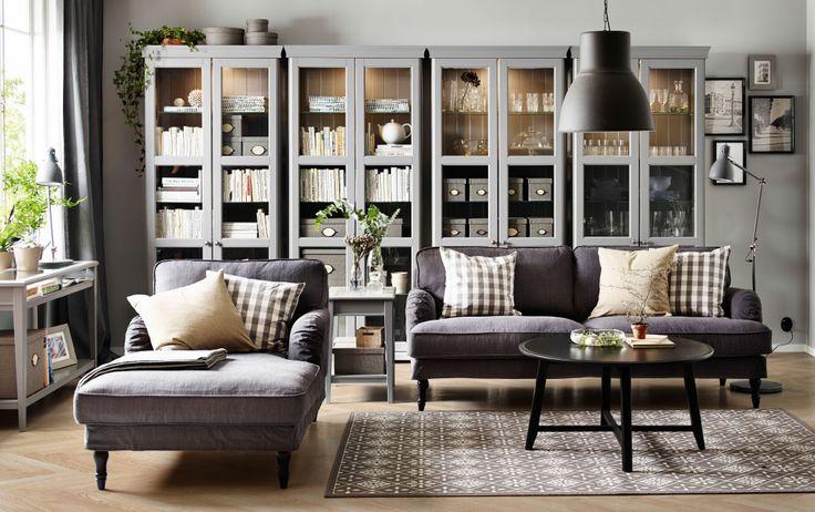 Salón con un sofá de tres plazas gris, un chaise longue, una mesa de centro redonda negra y cuatro vitrinas grises.