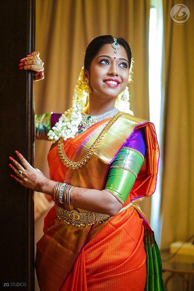 South Indian bride. Gold Temple jewelry. Jhumkis.Orange silk kanchipuram sarees.Braid with fresh flowers.Tamil bride. Telugu bride. Kannada bride. Hindu bride. Malayalee bride.Kerala bride.South Indian wedding.