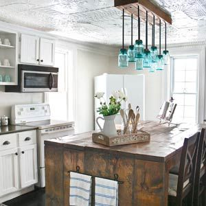 • Strip wallpaper, skim-coat plaster, paint $48 • Remove top-cabinet doors, create open shelves, add crown molding $20 • Finish lower doors with beadboard wallpaper & ¼-inch plywood; paint plywood, new hardware $152 • Use stone-look spray paint on countertops, & seal with on-hand polyurethane $29 • Cover floor with epoxy garage-floor paint $49 • Build island from pine planks, apply dark walnut stain $70 • Make pendant with 4x4s, curtain-rod extensions, & candelabra light sockets $100 Total…