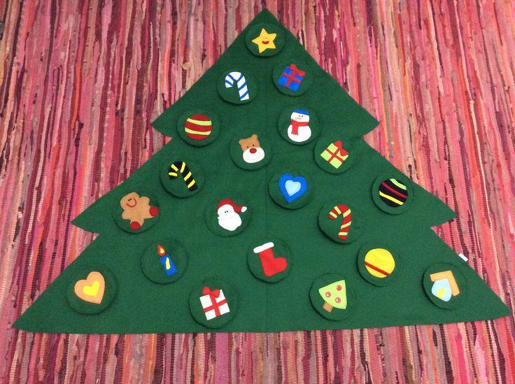 Árvore de Natal confeccionada com feltro. Adesivada, para colocar na parede (na altura da criança). <br> Acompanha 20 peças com velcro, para a criança enfeitá-la. <br>Prática e divertida, permite que os pequenos explorem o espaço e brinquem com as formas e figuras.
