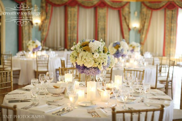 Wedding reception decor in white with accents of gold in the Cascade Ballroom at the Fairmont Banff Springs Resort; gold Chiavari chairs; gold Lida hurricane vases; centerpieces use blue hydrangea, yellow coxcomb, white hydrangea, white lisianthus, blue delphinium, and white roses; design and decor by Creative Weddings Planning & Decor (Photo courtesy of Tait Photography)