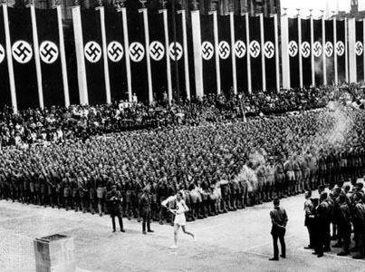 1936 – NAZISMO: chegada da tocha olímpica na abertura das Olimpíadas de Berlim em 1936.Como em todo o período Nazista na Alemanha, o aparato militar como forma de grandiosa propaganda era exposto além da própria suástica.