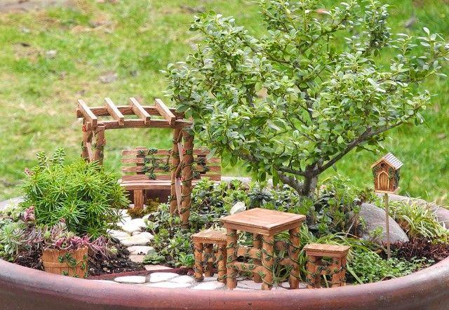 Pflanztopf dekorieren Gartenbank Holztisch Stühle kleiner Zierbaum