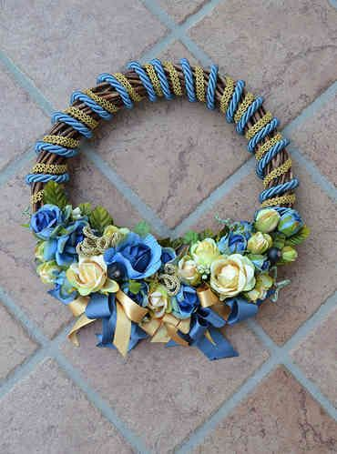 LARGE SIZED WREATH – Avion Blue - PatriziaB.com  Woven from wicker, wreath embellished with silk cordon spirals and a refined decoration of rosettes, berries and satin ribbons