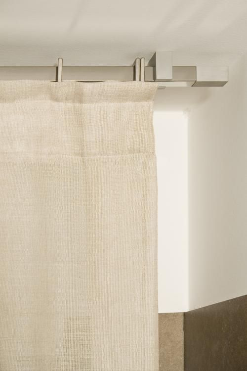 Particolare di tenda in tela di lino greggio, confezione a faldoncini, posa a soffitto su bastone di sezione quadra in acciaio lucido con particolari satinati. Realizzato da Tappezzeria Semenzato di Mestre
