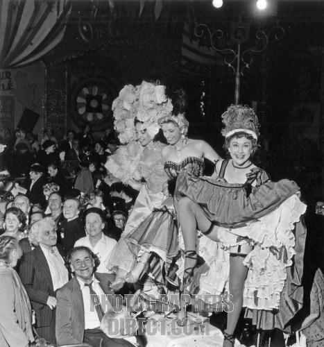 French cancan dancers performing on tables for an association reunion of elderly people at the Moulin Rouge , Paris , France on 13 July 1956