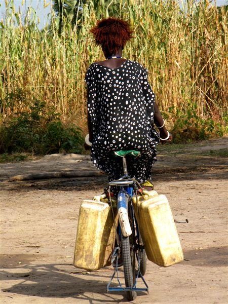 Sudan woman riding a bicycle with water containers attached on both sides.