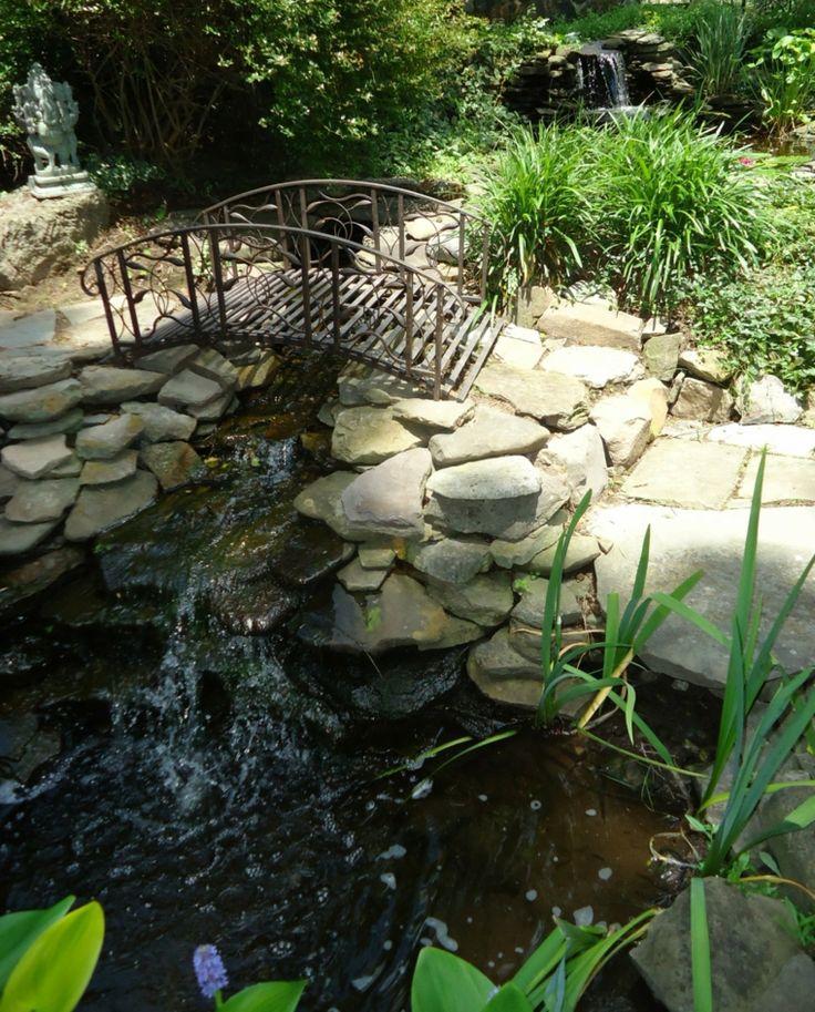 estanque con puente de piedra y cascada
