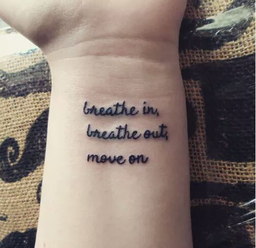Motivational words inked in black on the wrist