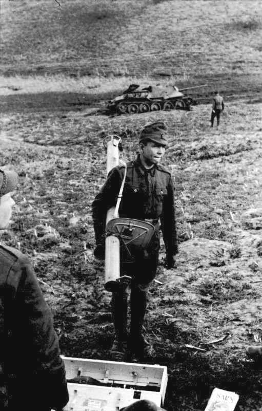 A Romanian soldiers with a Panzerschreck. In the background, a knocked-out SU-85 Tank Destroyer, presumably used for target practice.