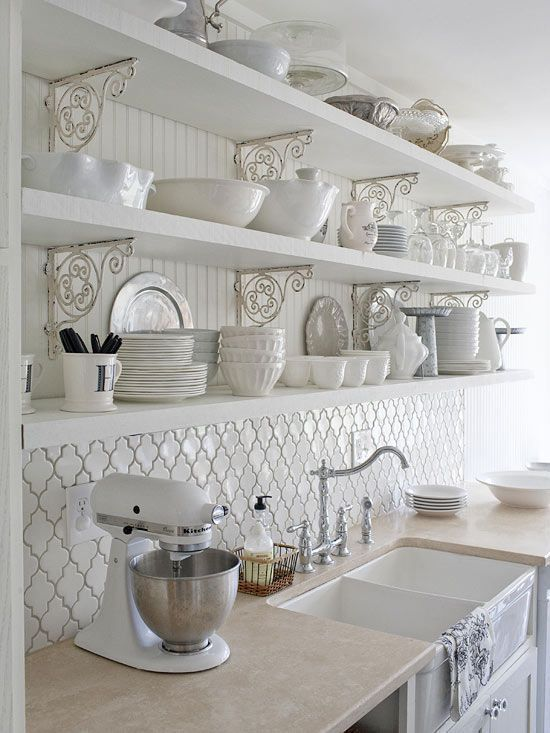 An all-white kitchen that oozes rustic country charm! You can create this look too by incorporating distressed scrolled brackets and open shelving. The tiled backsplash and beaded board upper wall add tons of visual interest.