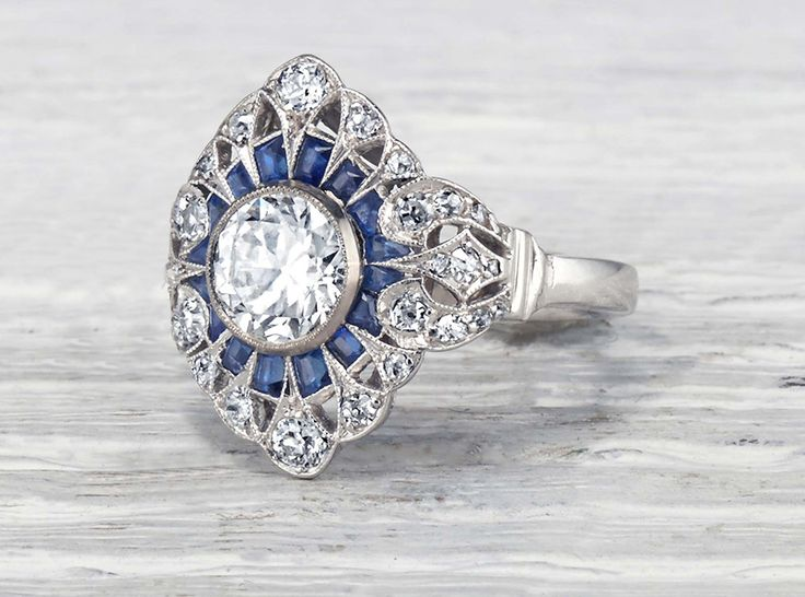 Antique Edwardian engagement ring made in platinum centered with a GIA certified 1.04 carat I color SI1 clarity old European cut diamond and accented with calibre cut sapphires and single cut diamonds