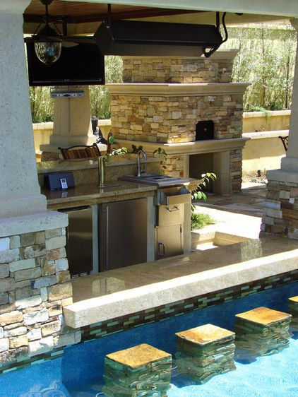Outdoor kitchen, equipped with a pizza oven, a swim-up pool bar, a mounted patio heater, ceiling fans.