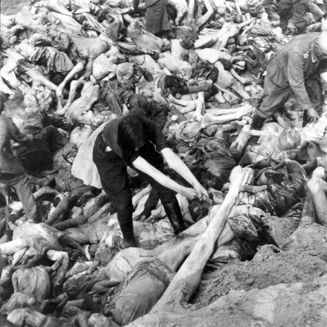 A female SS guard hauls a body into position in a mass grave for slain prisoners at the Nazi concentration camp in Bergen-Belsen, Germany, in April 1945. British troops liberated the camp on April 15.