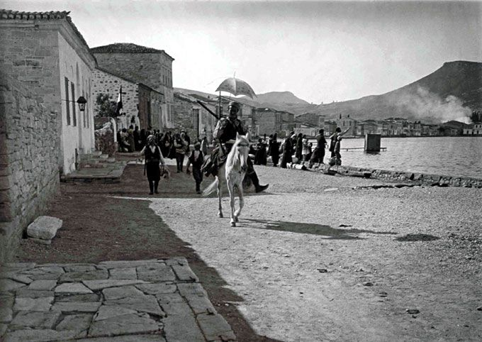 Turkish chettes (irregular armed forces) leaving Phocaea with their booty including an umbrella. In the background the house of Felix Sartiaux is seen with the French flag flying. A group of Greeks stand in front of the house for protection.