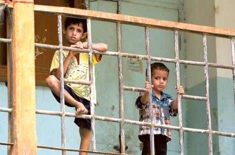 Boys look as they stand inside a school, used as a temporary shelter for internally displaced people (IDPs), in the southern Yemeni port city of Aden June 20, 2012.