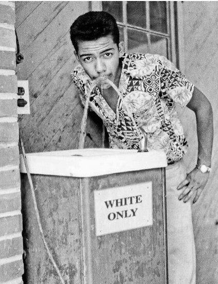 """Black man drinking at white only fountain, ca 1964 – by Cecil Williams  A black man fearlessly drinks out of a """"white only"""" water fountain when segregation was at its worst. This photo caught my eye because it displays something I haven't seen in many civil rights pictures: humor. He seems to almost be daring the person behind the camera to challenge him."""