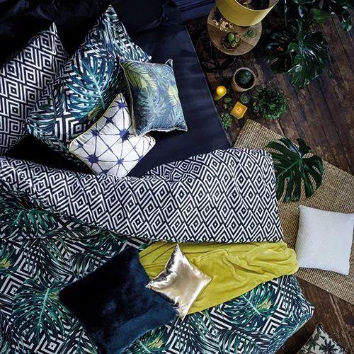 chambre tropicale linge lit coussins couette couleurs ethnique plantes vertes soie velours matiere couette housse taie oreillers plancher bois brut fonce motifs tropicaux