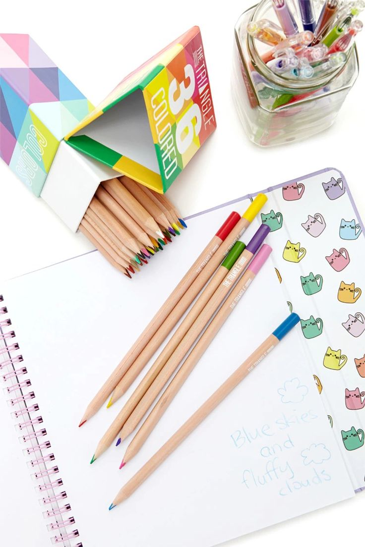 A set of colored pencils by Ooly™ featuring a triangular design for grip, multiple colors, and a triangle storage box with a rainbow geo print.
